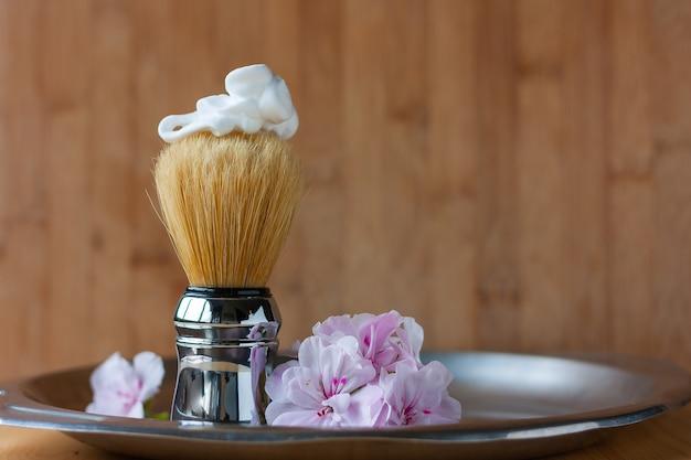 Pincel de barbear com espuma no topo em bandeja de aço envelhecido em madeira