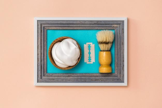 Pincel de barbear de barbear com espuma e uma lâmina na moldura contra a parede. o conceito de cuidados com o corpo. higiene. minimalismo.