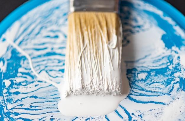 Pincel de close-up ou pincel com tinta branca na superfície da cerda e lata azul, pode