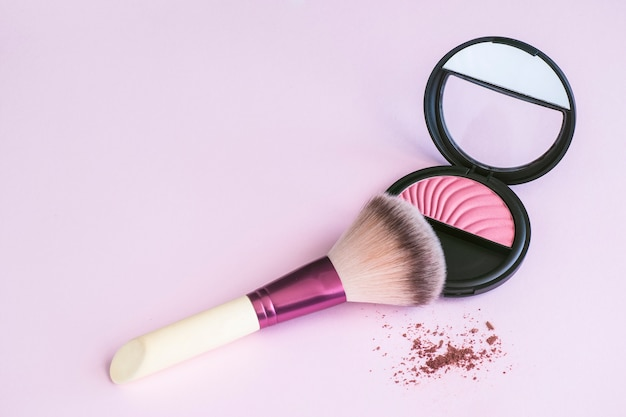 Pincel de maquiagem, apoiando-se em um rouge rosa em fundo rosa