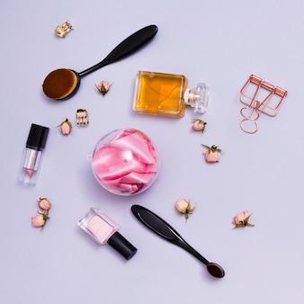 Pincel de maquiagem; batom; frasco de perfume; verniz de unhas e clutcher com rosas rosa em fundo roxo