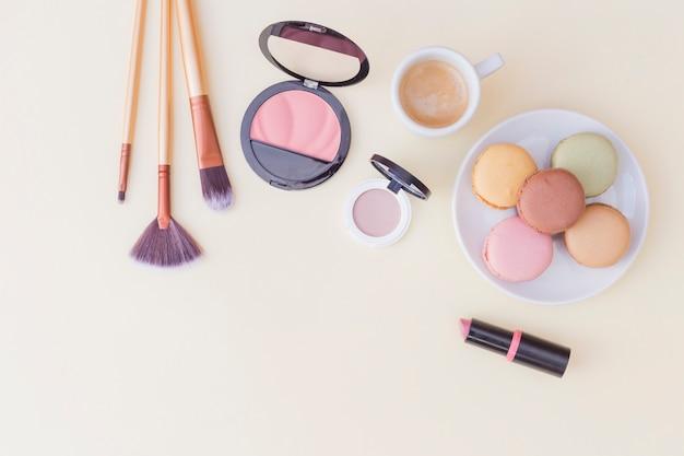 Pincel de maquiagem; blush e batom com café da manhã em fundo colorido