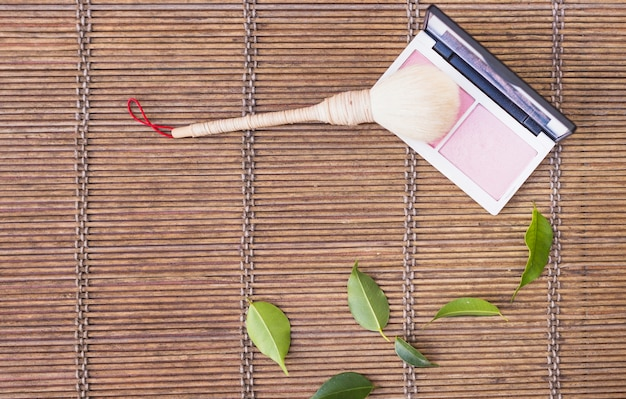 Pincel de maquiagem com blush de paleta em fundo de madeira