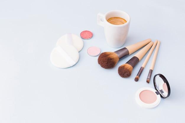 Pincel de maquiagem com esponja; sombra e blush com caneca de café sobre fundo branco