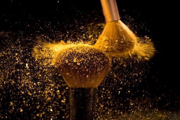 Pincel de maquiagem com pó cosmético dourado espalhando sobre fundo preto