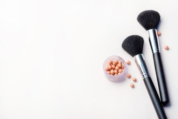 Pincel de maquiagem e blush em um fundo branco. conceito de beleza. close-up com espaço para texto