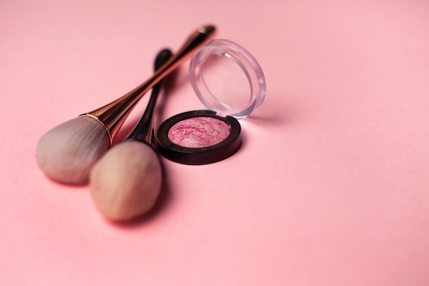 Pincel de maquiagem e blush em um fundo rosa. conceito de beleza. close-up com espaço para texto