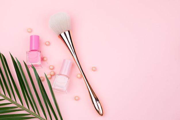 Pincel de maquiagem e esmaltes em um fundo rosa. close-up com espaço para texto.