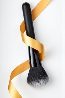 Pincel de maquiagem e fita dourada