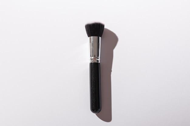 Pincel de maquiagem em fundo branco vista superior cosméticos e conceito de beleza