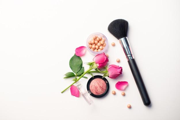 Pincel de maquiagem, flores e blush em um fundo branco. conceito de beleza. close-up com espaço para texto