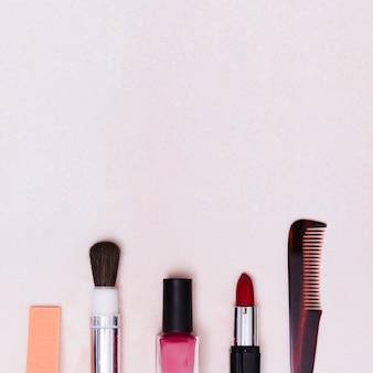 Pincel de maquiagem; frasco de verniz para unhas; batom e pente no pano de fundo texturizado branco