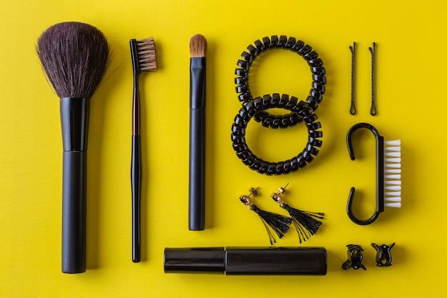 Pincel de maquiagem preta e cosméticos no plano amarelo leigos