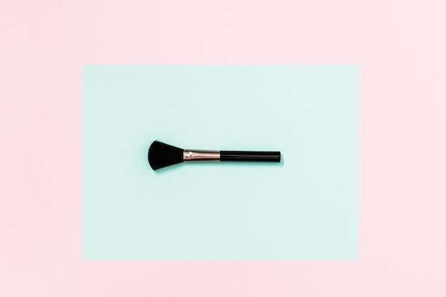 Pincel de maquiagem preta na cerceta e fundo rosa