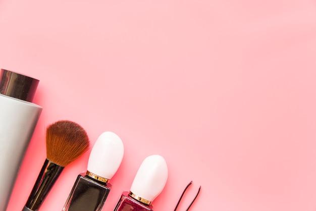Pincel de maquiagem; produto de cosméticos e pinças no pano de fundo rosa