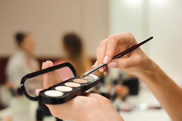 Pincel de maquiagem, produtos nas mãos, foto closeup