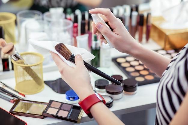 Pincel de maquiagem sendo borrifado com um líquido especial
