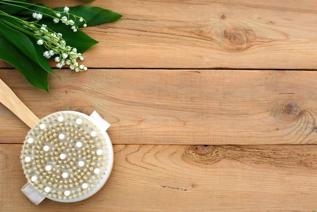 Pincel de massagem corporal redondo sobre madeira com folhas verdes e lírio branco.