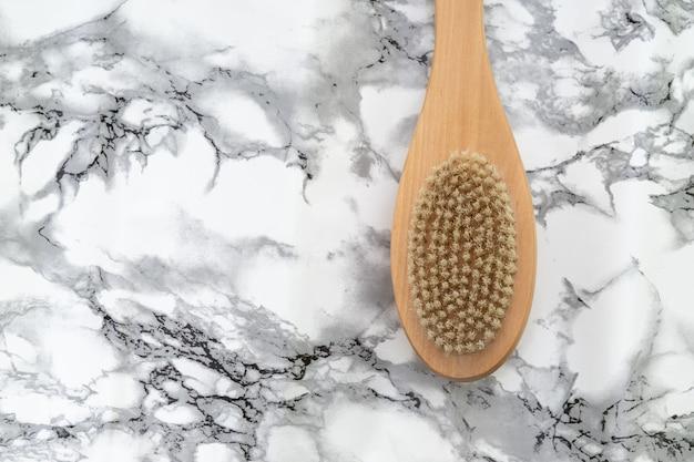 Pincel de massagem de madeira na parede de mármore branco