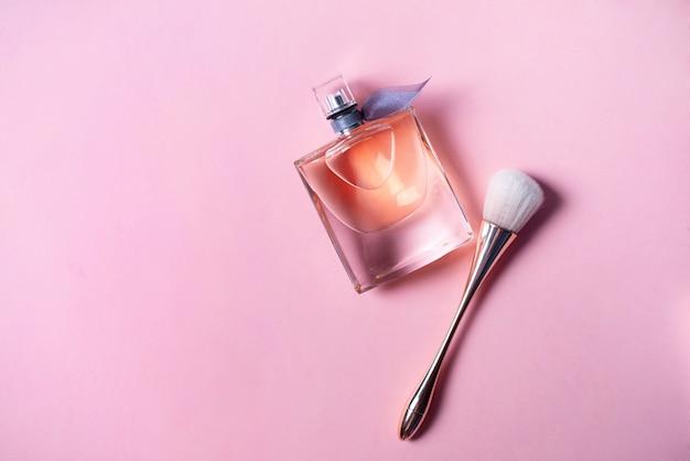 Pincel de perfume e maquiagem em fundo rosa. conceito de beleza.