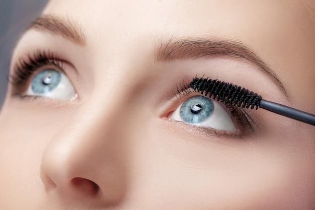 Pincel de rímel close-up. maquilhagem para olhos azuis. aplicação de rímel, cílios longos.