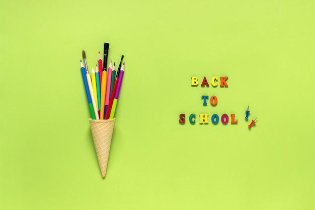 Pincel dos lápis dos artigos de papelaria no cone de gelado do waffle.