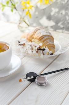 Pincel e sombras (batom) para sobrancelhas na mesa de café