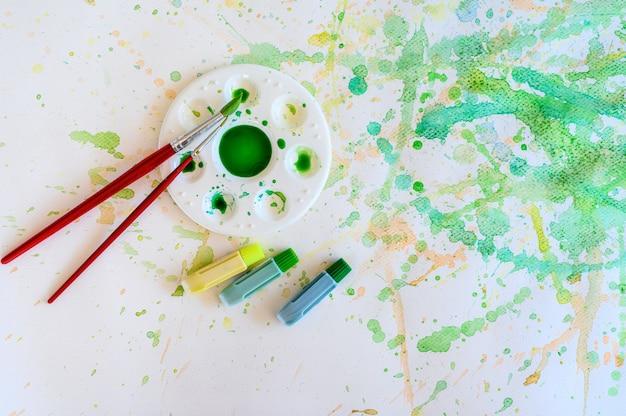 Pincel e tinta aquarela, paletas no papel branco mancham a cor, educação e objeto de arte.