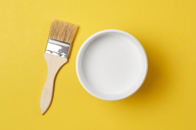 Pincel e tinta pode com cor branca sobre um fundo amarelo, vista superior