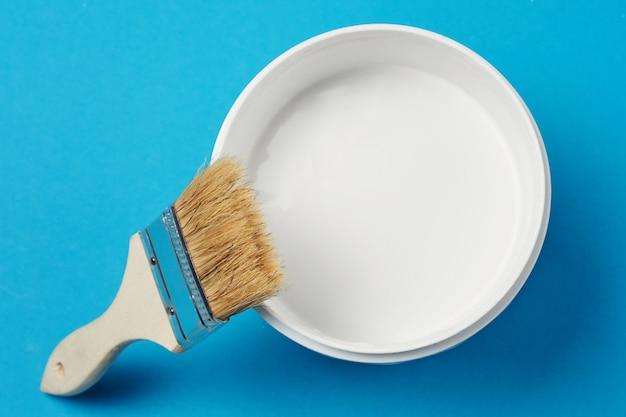 Pincel e tinta podem com cor branca sobre um fundo azul, closeup