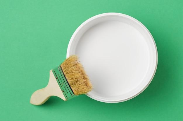 Pincel e tinta podem com cor branca sobre um fundo verde, vista superior