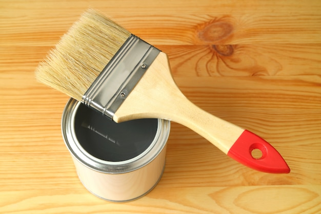 Pincel em uma lata de tinta aberta na prancha de madeira
