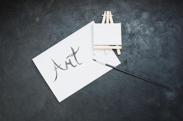 Pincel; mini cavalete e papel de texto de arte em fundo preto