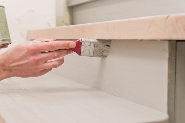 Pincel na mão, aplicando tinta em uma superfície de madeira durante o reparo