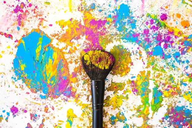 Pincel perto de borrões e montes de diferentes cores brilhantes e secas
