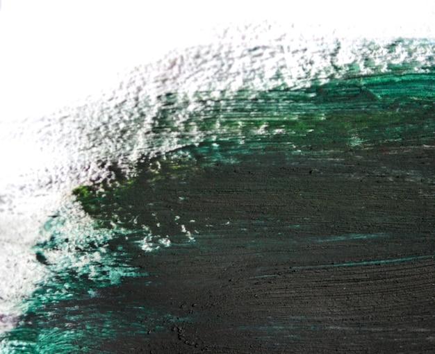 Pincel verde traça tintas a óleo em papel branco. isolado em um fundo branco. fundo criativo abstrato