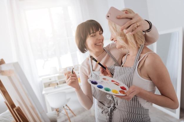 Pinceladas. artistas femininas talentosas e alegres juntas e sorrindo enquanto criam uma obra-prima