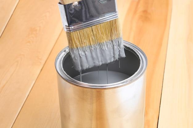 Pincele com lata de tinta na mão. um homem pinta pranchas de madeira com um pincel cinza.