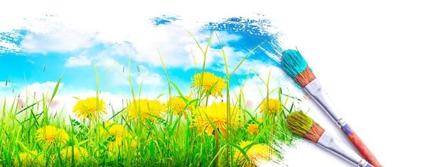Pincele com tinta azul sobre o céu e o campo verde.