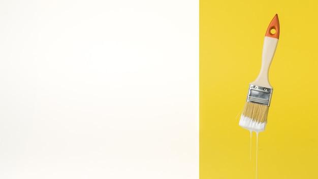 Pincele com tinta branca pingando sobre um fundo amarelo e branco. execução de trabalhos de pintura. lugar para texto.