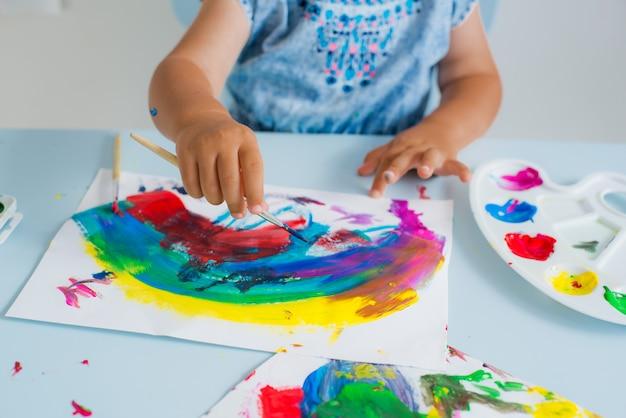Pincele com tinta na mão da criança