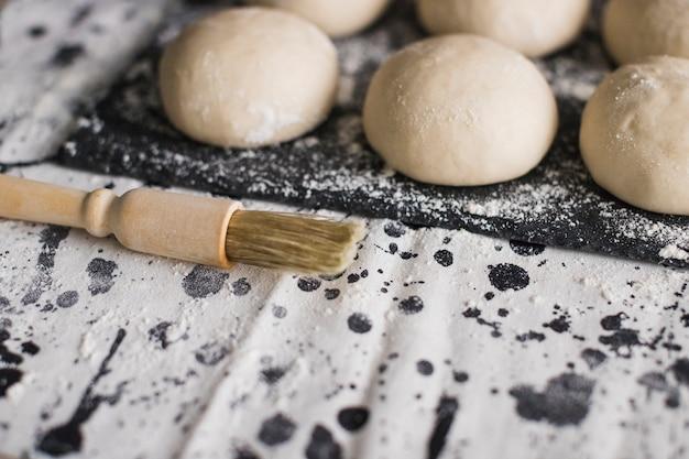Pincele perto do pão cru na ardósia com farinha