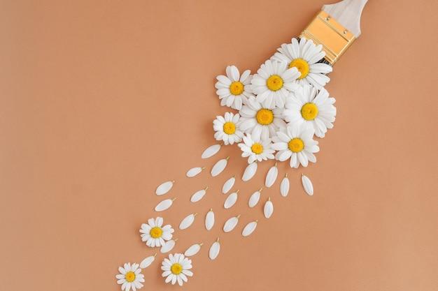 Pincele tintas com flores de camomila e pétalas, conceito de primavera em fundo pastel. liso plano da natureza mínima.
