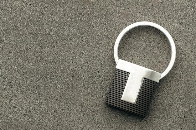Pingente de chave de metal em fundo escuro de concreto close-up