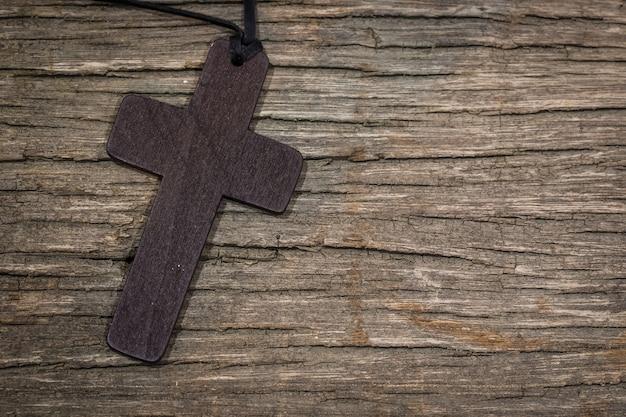 Pingente de cruz na mesa de madeira com espaço de cópia