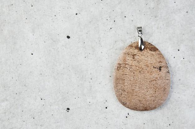 Pingente de jaspe bege em um cinza.