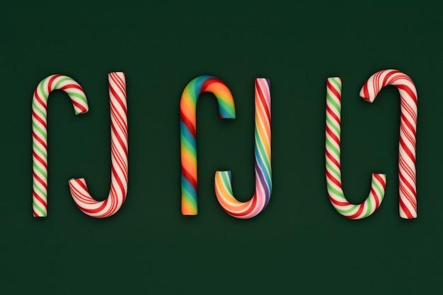 Pingentes de doces de natal sobre fundo verde. arco-íris e bastão de doces tradicional de ano novo.