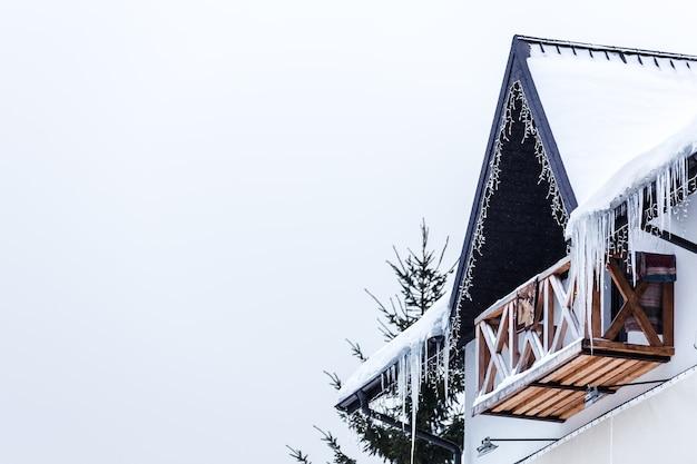 Pingentes de gelo no telhado coberto de neve