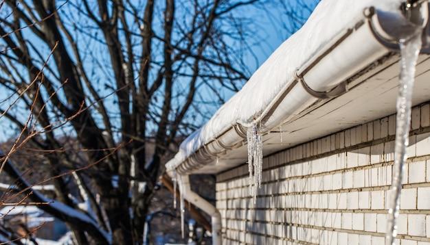 Pingentes de gelo nos telhados das casas
