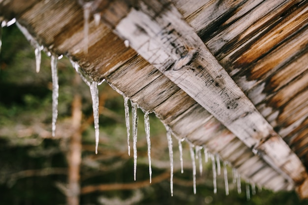 Pingentes de gelo pendurados em um telhado de madeira na primavera